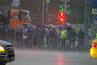 Rain during World Cup final. Russian police officers checking suspicious fans