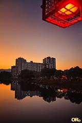 Sunset with red light (Otacílio Rodrigues) Tags: pôrdosol céu cidade água rio river reflexos reflections árvores trees prédios buildings urban luminária bridgelamp resende brasil oro luzes lights