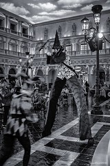 Stilted (evanffitzer) Tags: bw blackandwhite lasvegas vegas clown stilts drama juggling tourists tall fujix100s fujifilmx100s mono monochrome silverefxpro bizarre theatre live entertainment