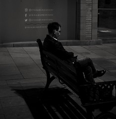 Reflections. (ianmiller6771) Tags: blackwhite nighttime afterdark man glasses shinyshoes thinking fuji 35mm streetphotography candid thoughtful reflective unhappy expression bodylanguage monochrome streetphotographyuk bw fareasternman blackandwhite
