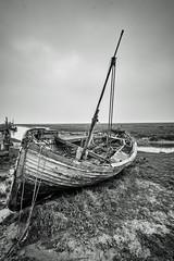 Old Fishing Boat (Geoffrey Tibbenham) Tags: fishing boat wreck timber rot mud coast north norfolk thornham blackandwhite monochrome portrait transport creek fuji ziess 12mm f28 openspace outdoor overcast countryside