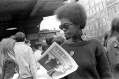 040870 10 (ndpa / s. lundeen, archivist) Tags: nick dewolf nickdewolf blackwhite photographbynickdewolf bw 1970 1970s 35mm film monochrome blackandwhite april cambridge massachusetts mass harvardsquare people woman youngwoman brunette glasses sunglasses shades natural afro sweater publication newspaper newsletter activist literature theblackpanther black africanamerican pin button freehuey hueynewtonbutton turtleneck phone telephone payphone phonebooth youngpeople building transitstation mbta mta t charlie pins buttons peacesign peacesymbol