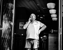 Grandeur (Kieron Ellis) Tags: man phone shorts teeshirt hat glasses doorway reflection lamps shadow light contrast candid blackandwhite blackwhite monochrome street