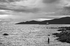 when you know your journey is long... (bluechameleon) Tags: sharonwish alone bluechameleonphotography clouds englishbay freighter landscape man mountains ocean rocks seawall ship silhouette summer sunset vancouver water waves ngc