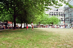 An island amidst the crowds (auqanaj) Tags: 20180616 kodakgold200 leipzig nikkor50mm114 nikonfe nikonseriese28mm128 cewescanat72dpi analog film street strase mutter kind fusball soccer football lunchbreak summer hot grass city people crowd leisure