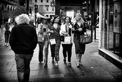 Doing it in style. (Mister G.C.) Tags: street urban photography blackandwhite bw leica leicamini leicaminiii elmar f35 primelens fullframe compactcamera compact camera autofocus autofocusing streetphotography urbanphotography shot image photograph candid people ladies females women fashion style eyecontact monochrome town city analog analogphotography analogue 35mm film kodakgold200 filmcamera schwarzweiss strassenfotografie mistergc glasgow scotland europe