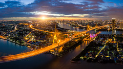 Aerial view of Bhumibol suspension bridge cross over Chao Phraya River in Bangkok city with car on the bridge at sunset sky and clouds in Bangkok Thailand. (MongkolChuewong) Tags: aerial aerialview architecture art asia auto bangkok bay bhumibol bhumipol bridge building car chaophrayariver city cityscape connect connection curve downtown drive drone dusk evening expressway freeway highway industry landmark landscape lane lighttrails motorway night panorama panoramic river roads route sunrise sunset suspension thailand traffic transport twilight urban view vision way krungthepmahanakhon th