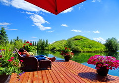 Nice to relax in the sun (peggyhr) Tags: peggyhr sister flowers dock judy sunshine lake trees umbrella dsc07167a bluebirdestates alberta canada blue green red hills reflections thegalaxy thelooklevel1red thegalaxystars heartawards level1peaceawards groupecharlie01