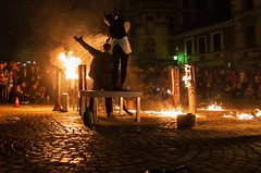 Water shower (Jumpin'Jack) Tags: people spectators watching woman standing ona table holding watering can sprinkling drenching man wearing business suit playing withthe fire logs burning street performance festival lent glavnitrg main square maribor slovenia