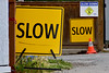 Slow (James_D_Images) Tags: sign warning slow slowdown repetition yellow black white blue fence wall alley street traffic cone