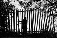 Fenced in Thoughts (JamieHaugh) Tags: wales uk gb great britain outdoors silhouette sony a6000 zeiss alpha ilce6000 black white monochrome bw thoughts fenced person cage trees figure thinking emotion dark chepstow locked blackwhite blackandwhite