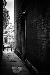 Through to St Mary's church (G. Postlethwaite esq.) Tags: bw derbyshire stmaryschurch wirksworth alley blackandwhite door flagstones hills lampost monochrome photoborder photowalk town tree