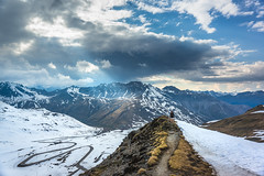 On Top Of The Pass (Tim Bellette) Tags: blue climb drama elevation female italianalps landscape mountain nature peak range rays road sky snow stelviopass sunlight swissalps valley windy yellow clouds person