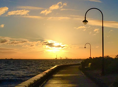 Sunset @ Elwood - appeared on ABC TV, 23 July 2018 (Marian Pollock) Tags: australia elwood victoria melbourne sunset walkway boardwalk lights sun lightshade cranes clouds sky shadows sea portphilipbay ocean