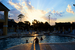 Pool At Dusk (Andy Zito) Tags: pool dusk setting sun brilliant rays son light up swimmers coming out beautiful sky water blues yellows through trees myrtle beach south carolina sheraton broadway plantation