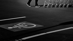 wheelchair and wheels (heinzkren) Tags: whells rollen räder parkplatz blackandwhite schwarzweis bw sw monochrome street streetphotography lines parking carpark feets shoes caddy trolley shopping panasonic lumix asphalt dark nike icon symbol pictogramm