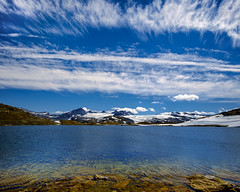 Jotunheimen National Park in Summer (Norway) (briburt) Tags: briburt fujifilm xe1 12mm wideangle samyang clouds light sun snow summer snowcapped zen peaceful tranquil stark rocks stones wet mountains jotunheimen nationalpark breheimen norway norwegian glacial water glacialwater blue glow sognefjellen sky azure panorama dramatic contrast skyscape landscape lake mountain peaks samyang12mm