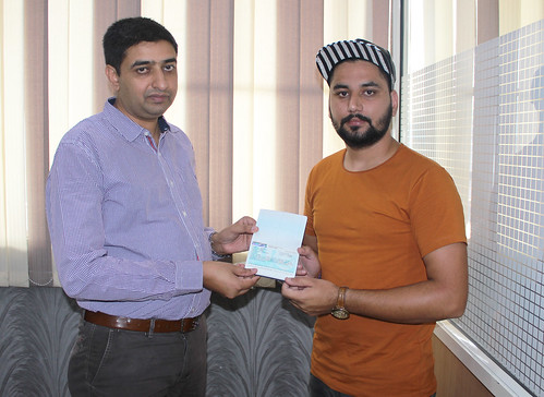 Gurvinder Kang (Director of West Highlander) handing over New Zealand Dependent Visitor Visa to Parwinder Singh