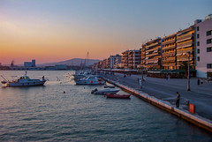 Volos Waterfront (Shawn Blanchard) Tags: volos greece greek grecian sunset sun boat water front pier mountain boardwalk buildings architecture sky blue red orange yellow europe