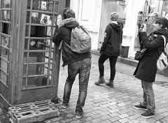 Have You Got My Best Side ? (tcees) Tags: argyllst london w1 soho sidewalk pavement man woman building wall phonebox people bag camera window cards x100 fujifilm finepix bw mono monochrome blackandwhite streetphotography street shop urban