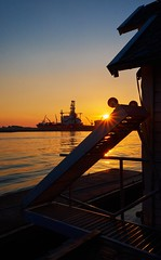 """Silhouettes"" (Vest der ute) Tags: xt2 norway rogaland haugesund sea water sky rig ship sunset sunstar ladder quay fence boathouse softlight evening fav25"