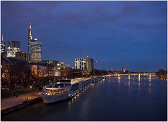 Blue Hour In Frankfurt (kurtwolf303) Tags: frankfurt city main river sky clouds ships harbour water buildings dusk blue blau dark dunkel kurtwolf303 olympusem5 omd microfourthirds micro43 persons mft cityscape schiffe brücke reflections spiegelungen dämmerung stadt himmel wasser gebäude personen fluss skyline bridge urban unlimitedphotos mirrorlesscamera