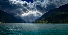 Storm Clouds and Light Rays on the Lustrafjord (briburt) Tags: briburt olympus em5ii clouds storm light sun lightrays summer fjord norway norwegian glacial water glacialwater blue glow sky azure panorama dramatic contrast mountains shore landscape mountain