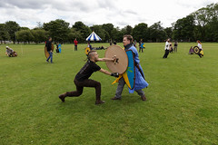 Historia Normannis Meadows June 2018-322 (Philip Gillespie) Tags: historia normannis central scotland sparring fighting shields swords axes spears park grass canon 5dsr men man women woman kids boys girls arms feet hands faces heads legs shins running outdoor tabards chain mail chainmail helmets hats glasses sun clouds sky teams solo dead act acting colour color blue green red yellow orange white black hair practice open tutorial defending attacking volunteer amateur kneeling fallen down jumping pretty athletic activity hit punch
