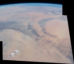 Mountain Arcs in the Sand (sjrankin) Tags: 21july2018 edited nasa iss iss056 iss056e95094 iss056e95096 panorama earthslimb africa saharadesert sand arid sanddunes mountains rockymountains rocky clouds round circular arc