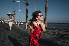 Little red dress (markfly1) Tags: girl child kid family sunny destination blue sky people walking little lady running sunglasses street moment full colour perfect timing woman with hat palm trees sea promenade seascape pavement shadow light red white polkadot grey candid nikon d750 35mm manual focus analog lens gorgeous morning paphos cyprus island life harbour happy smiling smile sunlight beautiful natural expression me kids nikkor secondhand streetphoto couple