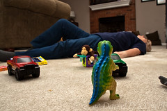 Playtime Takes its Toll (LongInt57) Tags: woman women person people mother grandmother babysitter toys dynosaur truck monkey car lying floor carpet rug lyingdown livingroom fireplace couch brown yellow green blue red play run fatigue
