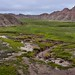 An Unnamed Creek Flowing through Prairie Grass and Badlands (Badlands National Park)