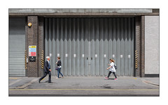 Concertina Doors, West London, England. (Joseph O'Malley64) Tags: concertinadoors collectionpoint businessentrance entrance exit businesspremises westlondon london england uk britain british greatbritain building brickwork bricksmortar cement pointing concrete steelreinforcedconcrete cladding compositecladding wiring electricalwiring electricalconduit burglaralarm shutter rollershutter hazardchevrons healthsafetysign dangersign healthandsafetyatwork nosmokingsigns signs signage patina oxidation rust rusting waterdamage ramp granitekerbing tarmac road doubleyellowlines noparkingatanytime parkingrestrictions passersby public membersofthepublic people mobilephones bags urban urbanlandscape architecture architecturalphotography street streetphotography fujix fujix100t accuracyprecision shadows