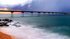 A cloudy and threatening dawn (Fnikos) Tags: sea water mar mare dawn wave rock bridge puente pont pier sky skyline cloud cloudy architecture construction bay outdoor