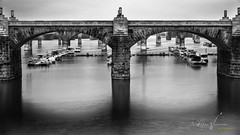 """""""The City of Bridges"""" (The Youngturk) Tags: bridge river footbridge canal arch pier tourboat reflection suspension railway elevated walkway flowing water long exposure blackandwhite"""