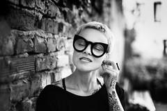 (uerbe) Tags: monochrome mono black blackandwhite blackwhite portrait people woman face eyes eyewear glasses street alley dress expression tattoo tattoos tattoed pierced