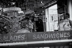 Framed By Salades And Sandwiches (Alfred Grupstra) Tags: blackandwhite people urbanscene men citylife street editorial store outdoors city women hoorn nl