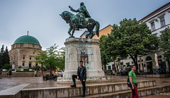 2018 - Hungary - Pécs - Hunyadi János (Ted's photos - For Me & You) Tags: 2018 cropped hungary nikon nikond750 nikonfx pécs tedmcgrath tedsphotos vignetting jánoshunyadi jánoshunyadistatue pecshungary statue horse széchenyisquare pecsszéchenyisquare széchenyisquarepecs mosqueofpashaqasim mosqueofpashaqasimpecs mosque dome church pálpátzy pálpátzystatue bronze bronzestatue people umbrella pathsandpeople