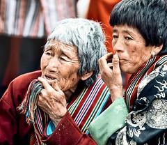 Bhutan: Elders I. (icarium.imagery) Tags: bhutan canoneos5dmarkiv bhutanese buddhist captureone drukyul expression festival gasafestival gasatshechu gasavalley gazing himalayas localpeople naturallight portrait red rural sigma sigma100400mmf563dgoshsm spectators streetportrait street traditional traditionalclothing traditionaldress travel two vibrant warmlook greyhair old women
