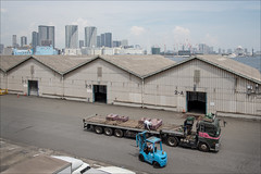kaigan-1789-ps-w (pw-pix) Tags: sheds warehouses stores 2a 2b 2c doors cones barrier wall truck trucks semitrailer forklift forklifttruck concrete asphalt bitumen tyremarks water bay tokyobay skyline cityskyline tokyoskyline portarea buildings city suburbs cranes construction olympicvillageconstruction ship industry industrial transport shipping clouds sky sunny hot humid haze hazy viewfromhinodestation viewfromyurikamome hinodestation kaigan minatoku tokyo tokyoto japan