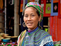 2018-03d Northeast Vietnam (61) (Matt Hahnewald) Tags: matthahnewaldphotography facingtheworld character head face eyes catchlights mouth teeth goldtooth silver earrings wrinkles expression lookingcamera smile story tribal attire embroidery clothing garment headscarf consent humanity living work travel culture tradition ethnic minority rural traditional cultural tuesday weekly folklore background market village cocly laocai vietnam northern hmong individual oneperson female middleaged woman photo detail faceperception physiognomy nikond3100 primelens nikkorafs50mmf18g 50mm 4x3 horizontal street portrait closeup headshot threequarterview outdoor color colorful posing authentic smiling clarity