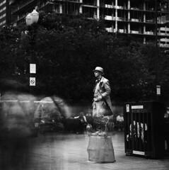 As still as... (Zeb Andrews) Tags: hasselblad500c portland kodakektar100 mrstatue oregon downtown urban streetperformers longexposure film 6x6 mediumformat pacificnorthwest ndfilter scannedatbluemooncamera nikoncoolscan9000 zaahphoto waiting crowds filmisnotdead streetscenes