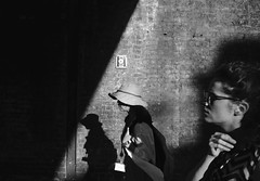 Out of the shadows (mesbkr1) Tags: canonphotography bnwphotography blackandwhitephotography bnw streetphotographymagazine canon streetphotography blackandwhite camdentown wall hat tourist people shadows london