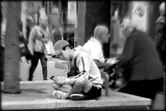 Bubble dweller (* RICHARD M (7.5 MILLION VIEWS)) Tags: candid street portraits portraiture streetportraits streetportraiture candidportraits candidportraiture mono blackwhite bubble bubbles cap baseballcap oblivious smartphones alteredstates earphones headphones liverpool merseyside crosslegged crossedlegs squatting squatter seated shorts unaware shopping shoppers isolation isolated wires oblivion alone absorbed concentration expressions technology