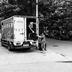 Family business (Go-tea 郭天) Tags: qingdaoshi shandongsheng chine cn qingdao huangdao shandong truck delivery delivering tires unloaded unload unloading help helping support suporting suported familly young old boy man woman lady mother son together business work working busy duty 2 heavy strong hard parked sidewalk pavement hot summer street urban city outside outdoor people candid bw bnw black white blackwhite blackandwhite monochrome naturallight natural light asia asian china chinese canon eos 100d 24mm prime