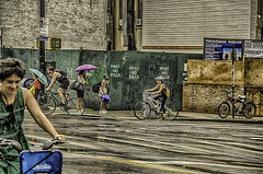 """Street Scene at Corner of Grand and Essex Street LES after Summer Rain Storm (nrhodesphotos(the_eye_of_the_moment)) Tags: dsc73223001084 """"theeyeofthemoment21gmailcom"""" """"wwwflickrcomphotostheeyeofthemoment"""" streetscene les essexandgrandstreets candid people summer bikers umbrella bikes metal outdoor wall signs street buildings streetlights texture"""