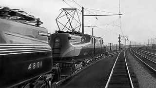 Pennsylvania Railroad GG-1 electric locomotives # 4844 & # 4801, are seen while spotted on siding, ca early 1940's