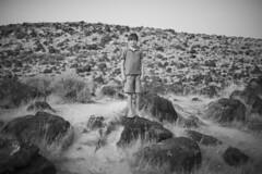 Rock Field Boy (JasonCameron) Tags: monochrome black white bw kid pose background cement desert lava rocks hill mount