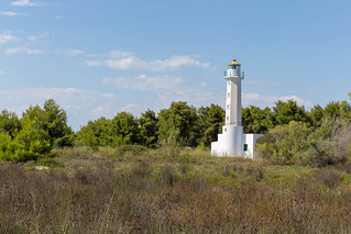 White lighthouse close to the beach