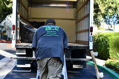 Mover unloading a Rental Truck (hireahelper) Tags: moving mover truck outdoors sun green street summer people road